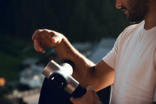massage gun on forearm